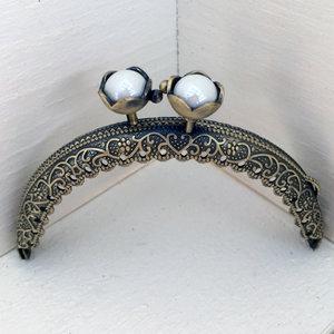 Sirligt portmonnäknäppe med vita pärlor